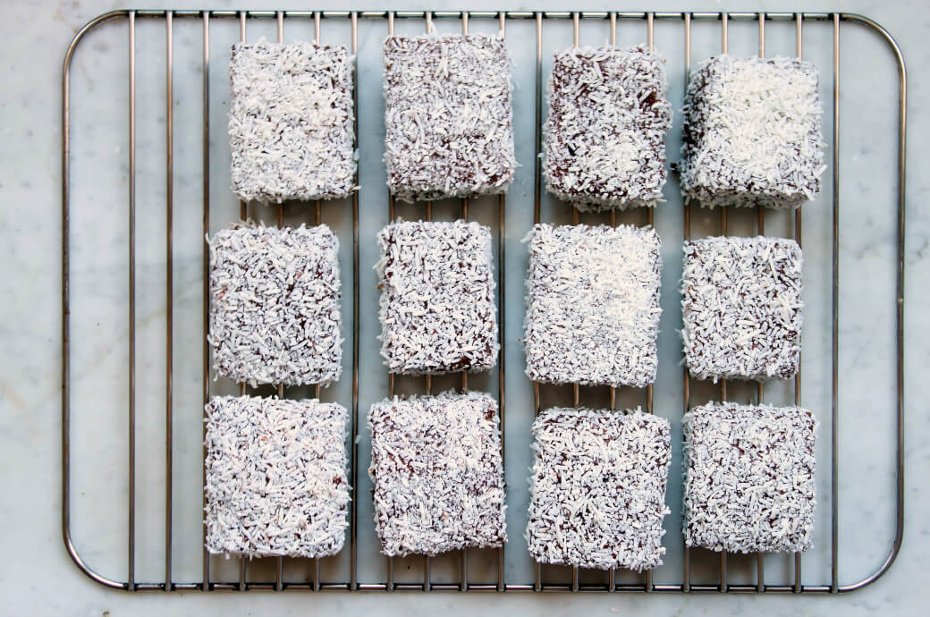 Twelve chocolate and coconut covered lamingtons on a rack.