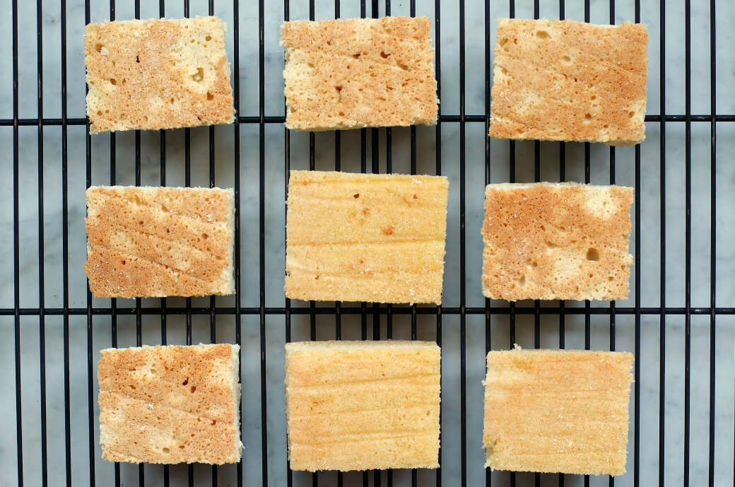 Nine squares of sponge cake on a rack.