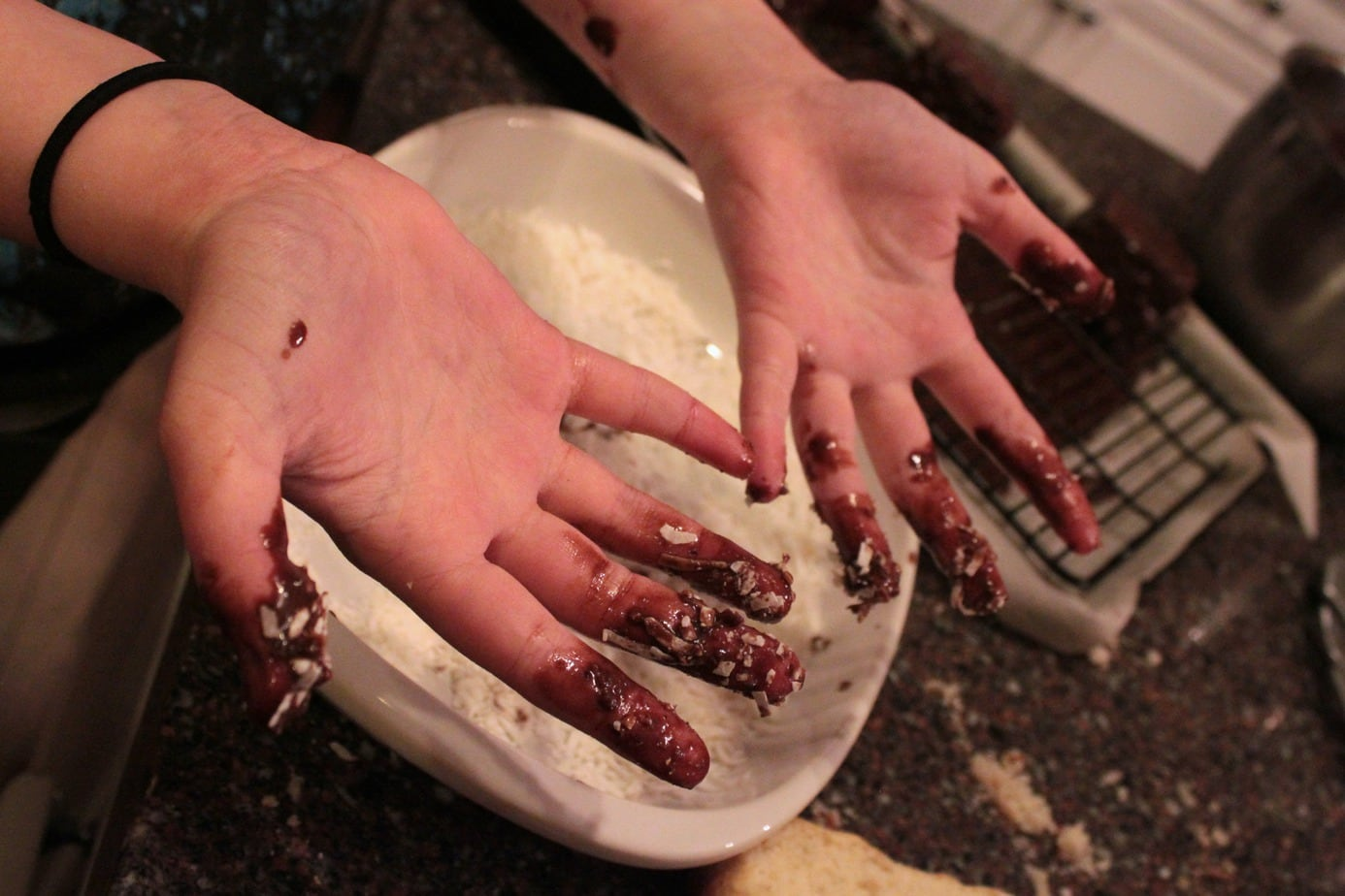 A pair of hands decorated in chocolate and coconut.