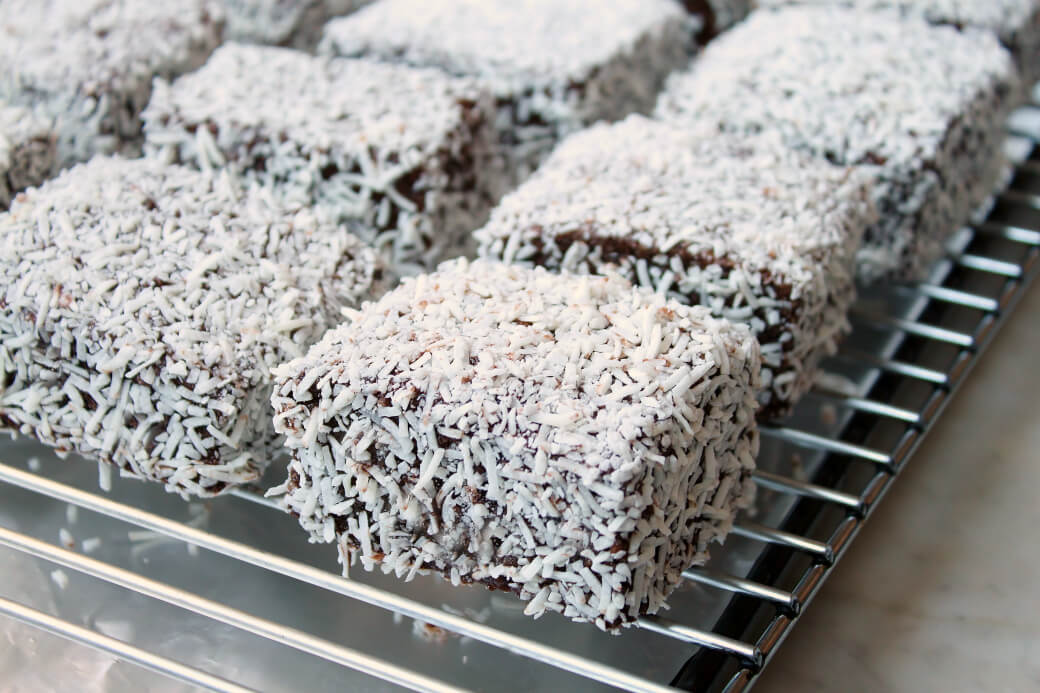 Six chocolate and coconut covered lamingtons on a rack.