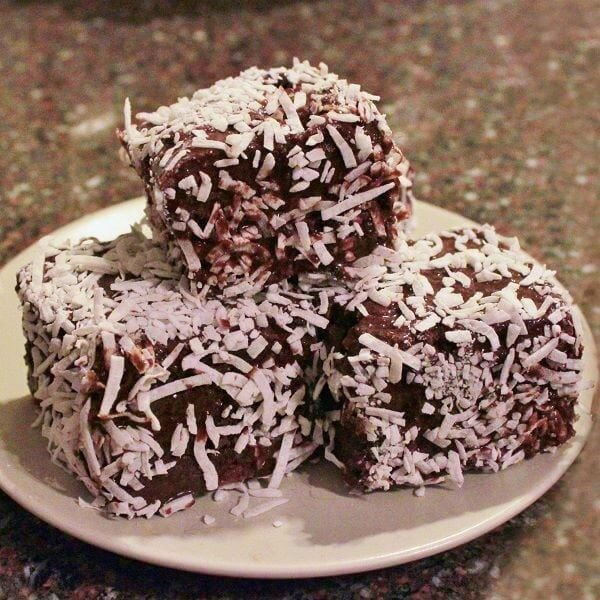 A small white plate holds 3 lamingtons.
