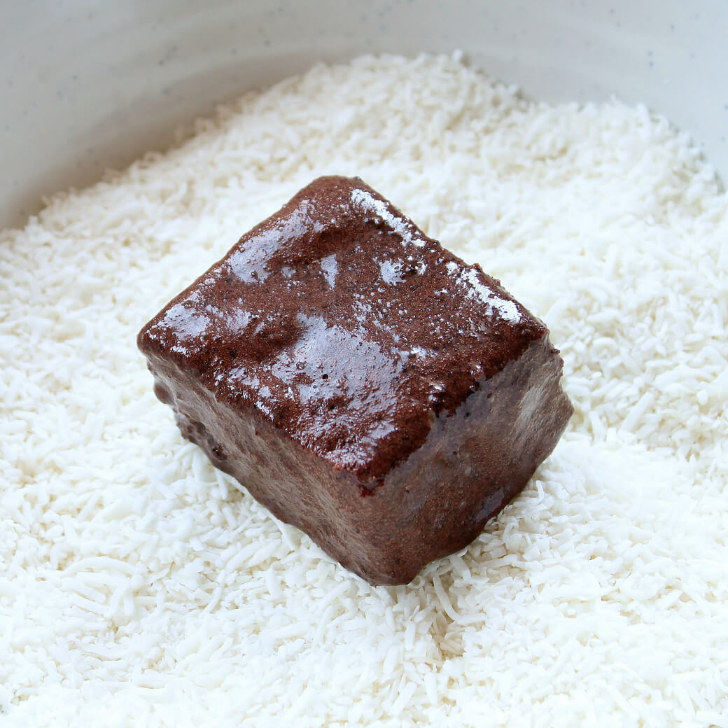 A square of chocolate covered sponge cake sits in a bowl of dessicated coconut.