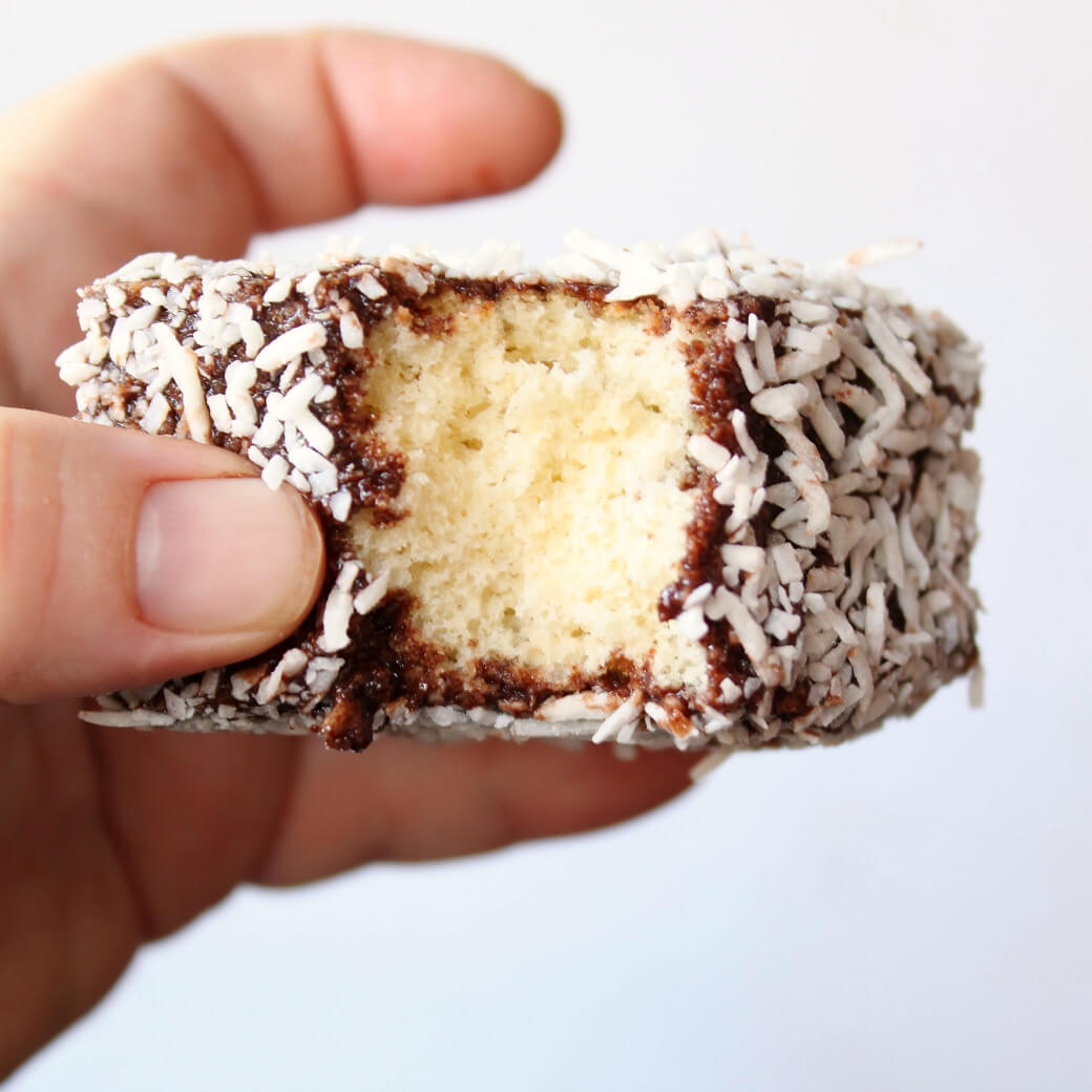 A hand holds a piece of chocolate and coconut covered sponge cake with a bite out of it.