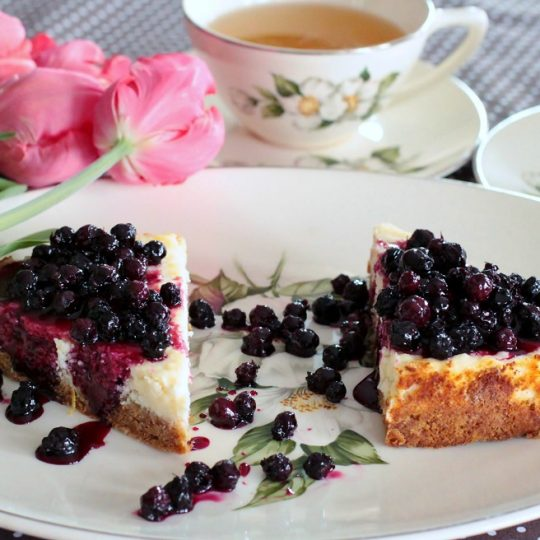Two slices of lemon cheesecake topped with juicy purple Saskatoon Berry Sauce surrounded by cups of tea and pink tulips.