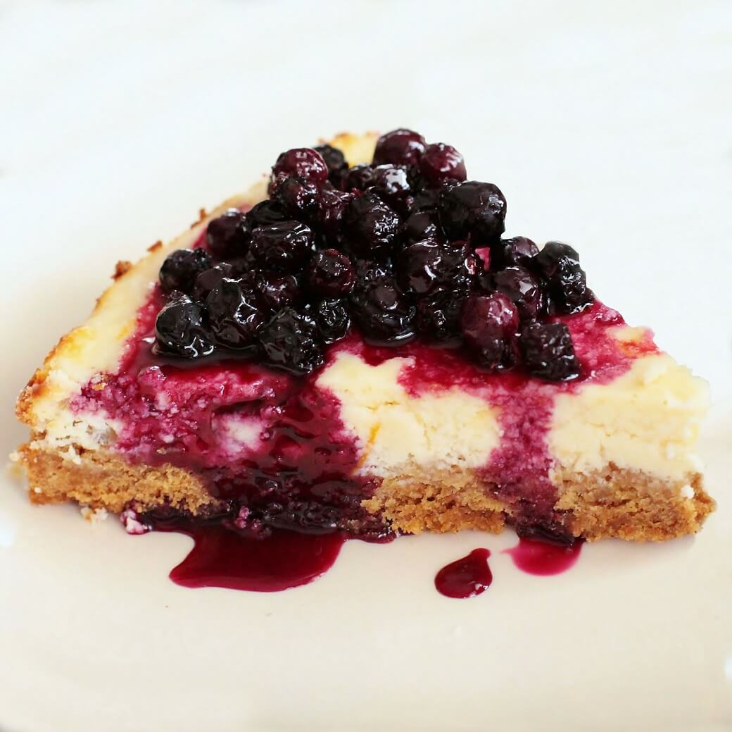 a single slice of lemon cheesecake topped with juicy purple Saskatoon Berry Sauce.