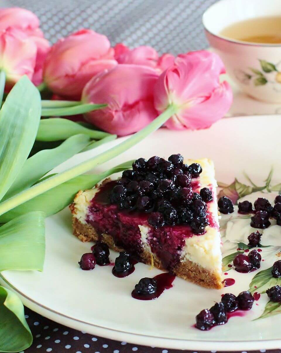 A slice of lemon cheesecake topped with juicy purple Saskatoon Berry Sauce surrounded by cups of tea and pink tulips.