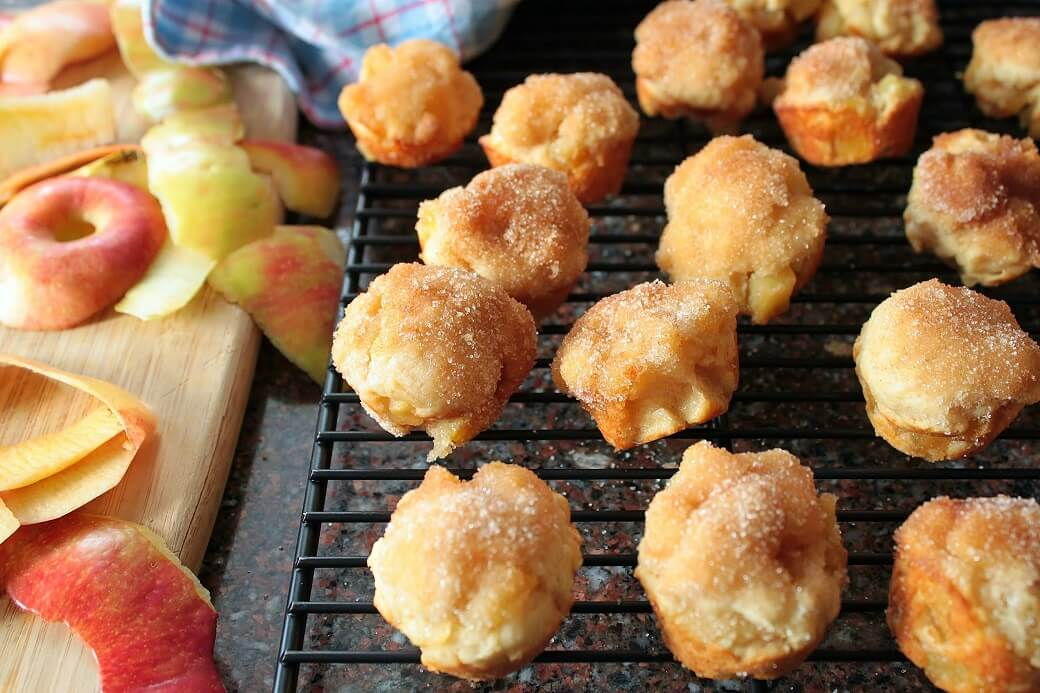 Apple Fritter Bites - Dish 'n' the Kitchen Golden baked apple fritters with chunks of apple sit on a black cooking rack. Apple peelings sit beside.