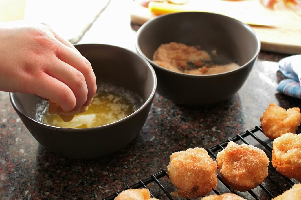 Apple Fritter Bites - Dish 'n' the Kitchen a hand dips a golden mini fritter into a bowl of melted butter. A bowl of cinnamon sugar waits nearby.