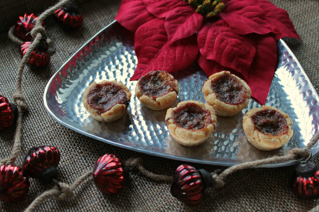 Butter Tarts on a silver serving tray surrounded by a red poinsetta and Christmas decorations.