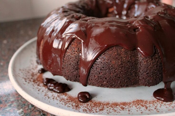 A chocolate bundt cake with glossy chocolate glaze dripping down.