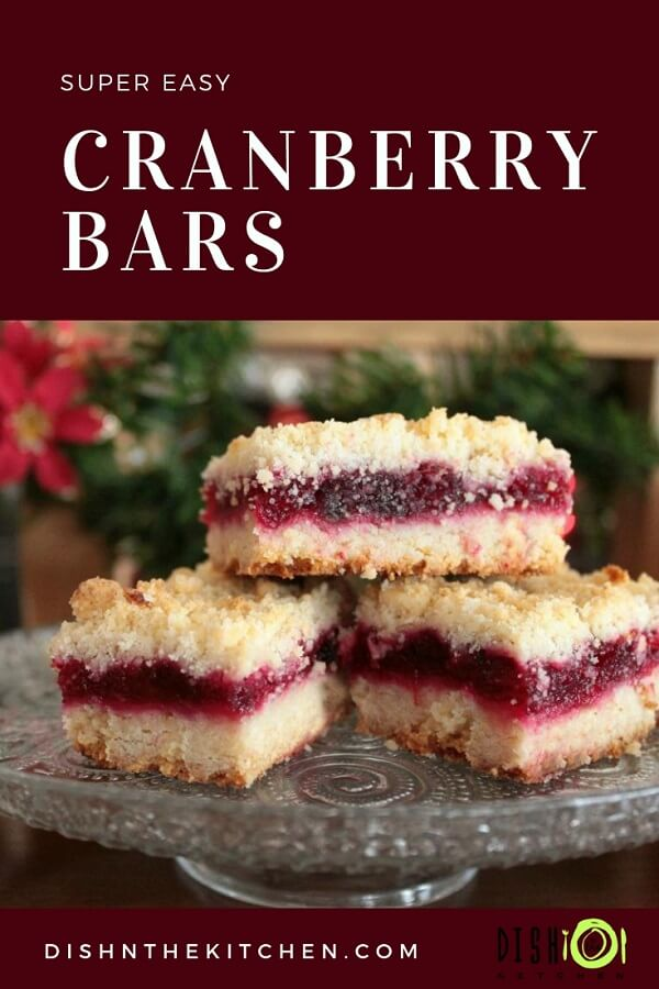 Pinterest image of three layered golden Cranberry Bars with a ruby red filling on a shiny glass plate.