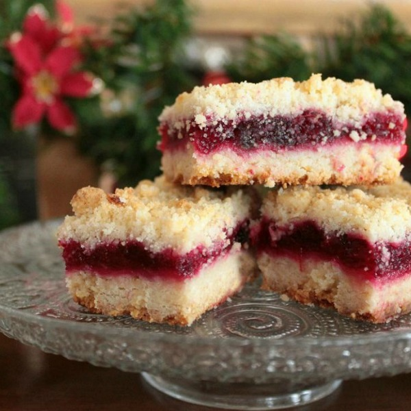 Cranberry Bars - Three golden bars with a ruby red middle layer on a sparkling glass platter.