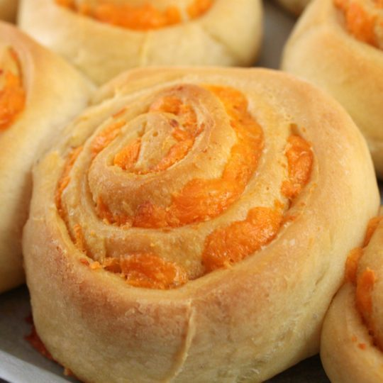 Cheesebuns - Dish 'n' the Kitchen Close up of a round scrolled baked bun filled with cheddar cheese.