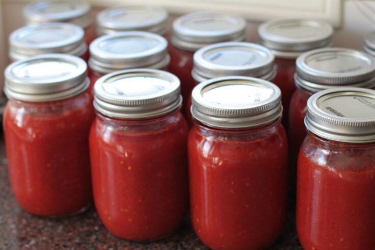 Jars of bright red Roma Tomato Passata Sauce on a kitchen counter.