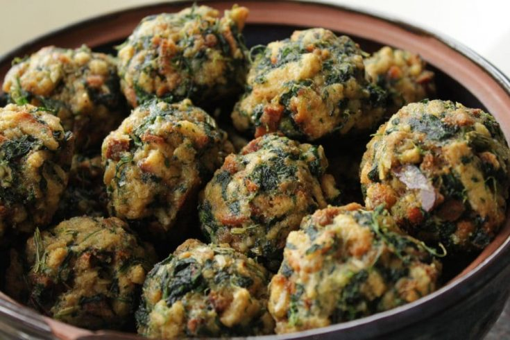 A bowl full of baked stuffing balls dotted with spinach.