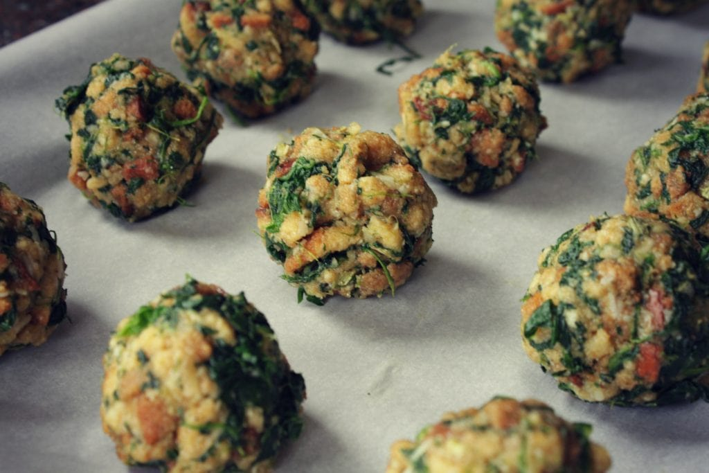 Stuffing balls dotted with spinach on a baking sheet.