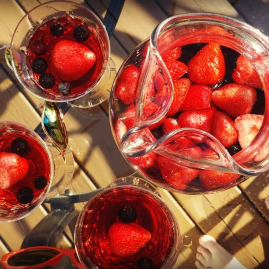 A pitcher and three glasses full of Berry Rosé Sangria.