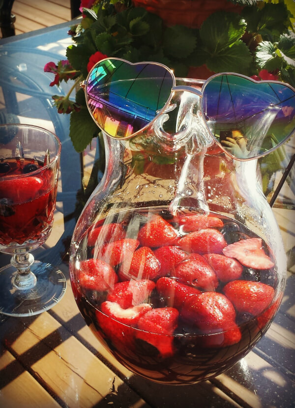 A glass pitcher of Berry Rosé Sangria with a pair of heart shaped sunglasses.