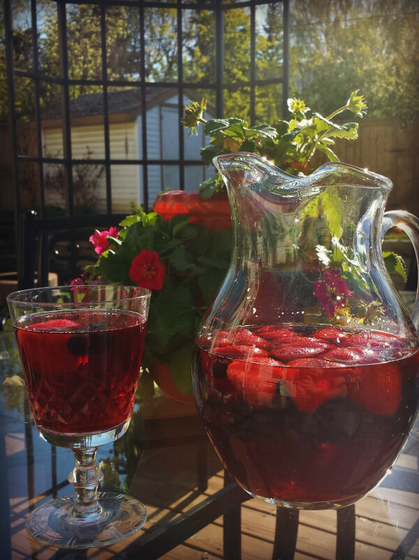 A pitcher of red Sangria and berries sits on a glass table during a sunny day.