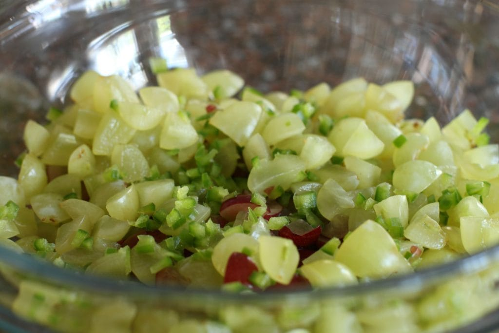 A bowl of chopped grapes and jalapenos.