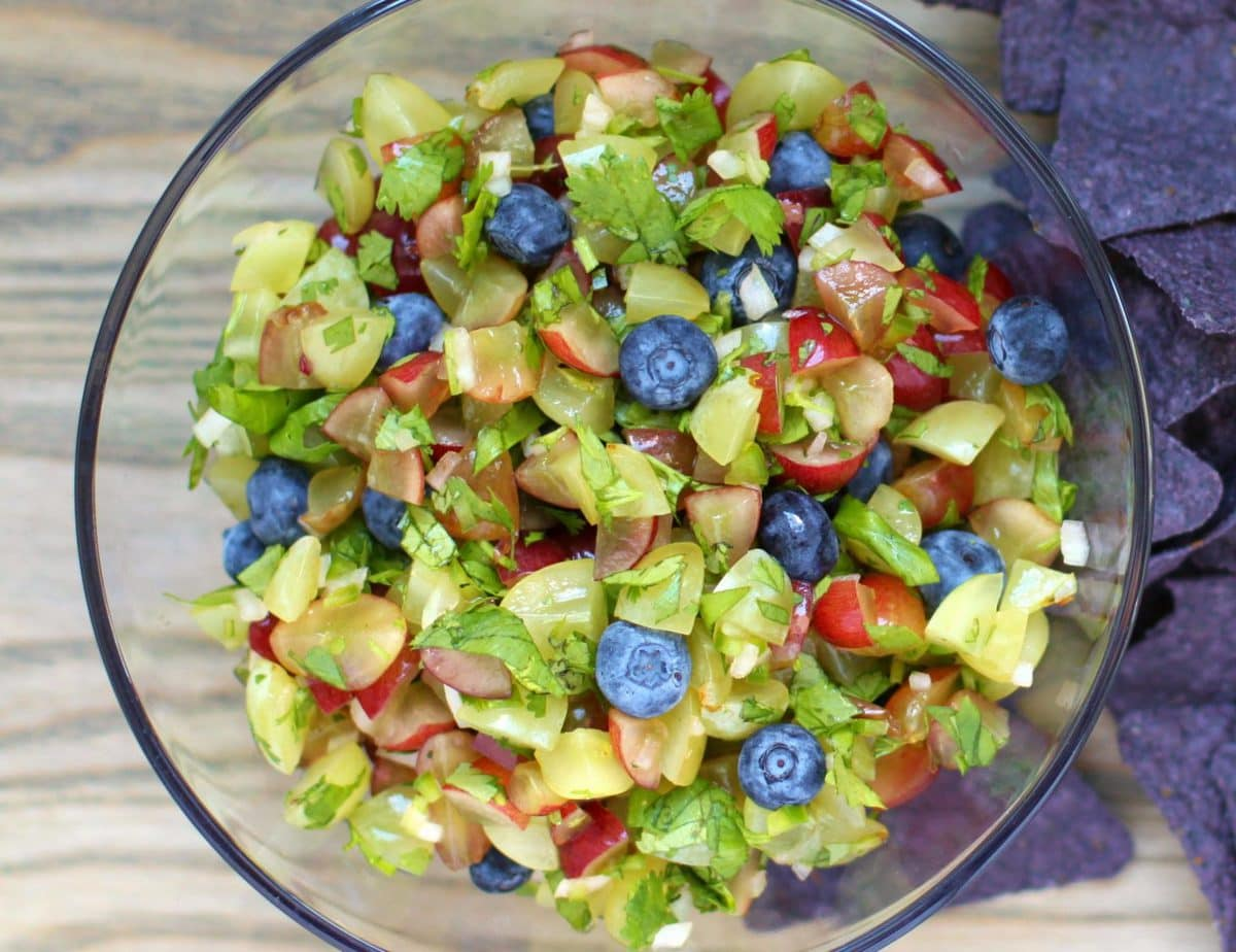 A bowl full of salsa made from chopped green and red grapes with blueberries and cilantro.