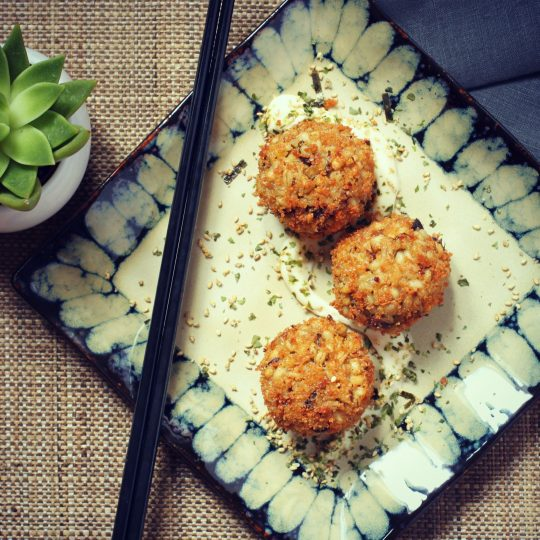 Three Golden balls of Barley Arancini with Shiitake Mushrooms & Seaweed on a square plate.