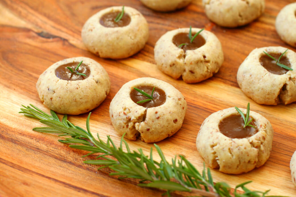 Pecan Polvorones - Caramel filled cookes topped with a sprig of green rosemary on a wooden platter.