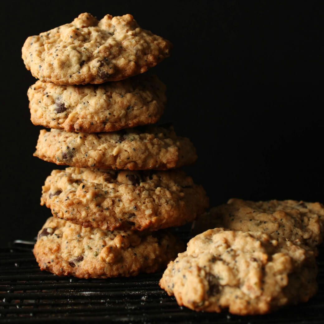 A stack of chocolate chip cookies on a black background.