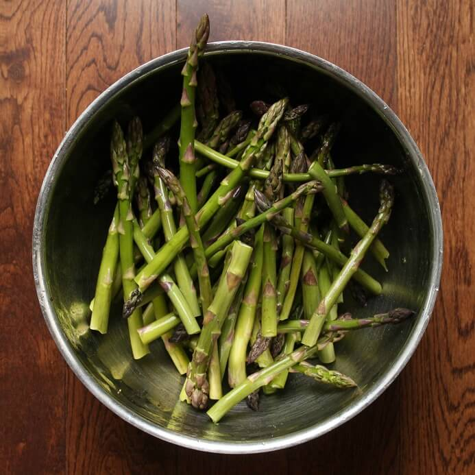 A bowl containing fresh green asparagus