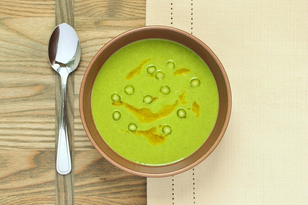 A bowl of bright green asparagus soup
