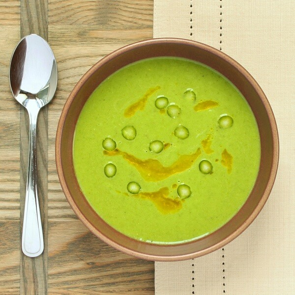 A brown bowl full of bright green asparagus soup.