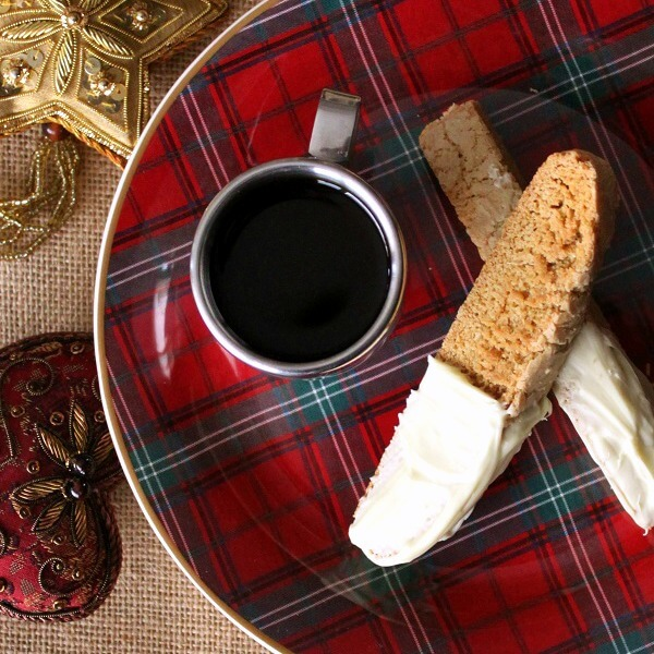 Cookinotti Biscotti - Two white chocolate dipped biscotti sit on top of a plaid plate with a cup of espresso.