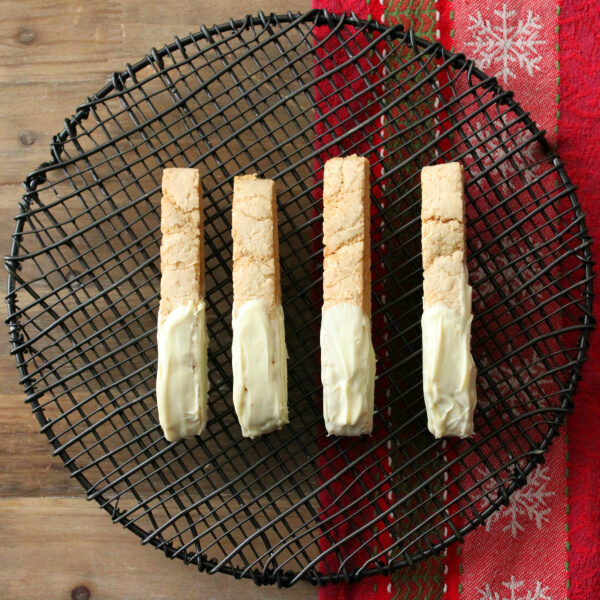 Cookinotti Biscotti - Four white chocolate dipped biscotti sit on top of a black cooling rack.