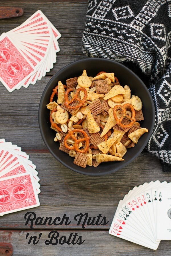 Ranch Nuts 'n' Bolts -Dish 'n' the Kitchen Pinterest image of a black bowl of mixed cereals, nuts, and chips sits surrounded by playing cards and a napkin.
