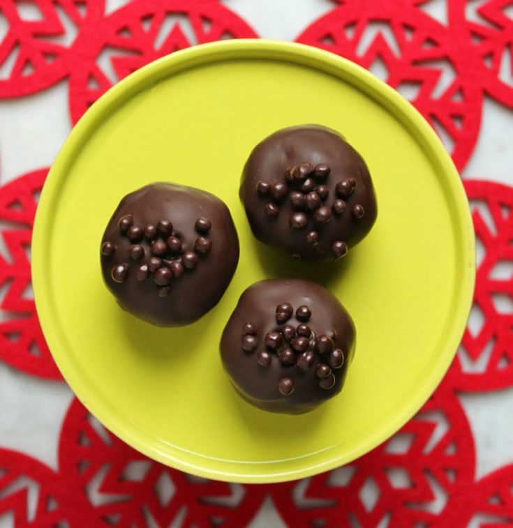 Three chocolate covered Nanaimo Truffles on a bright green plate sit on a red doily.