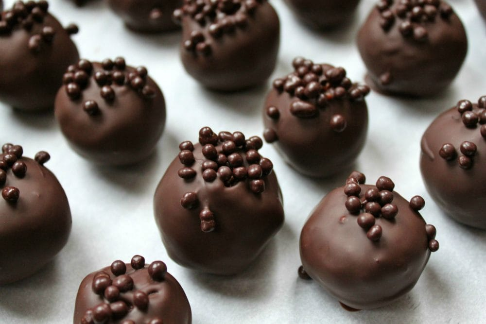 Chocolate covered Nanaimo Truffles on parchment paper.