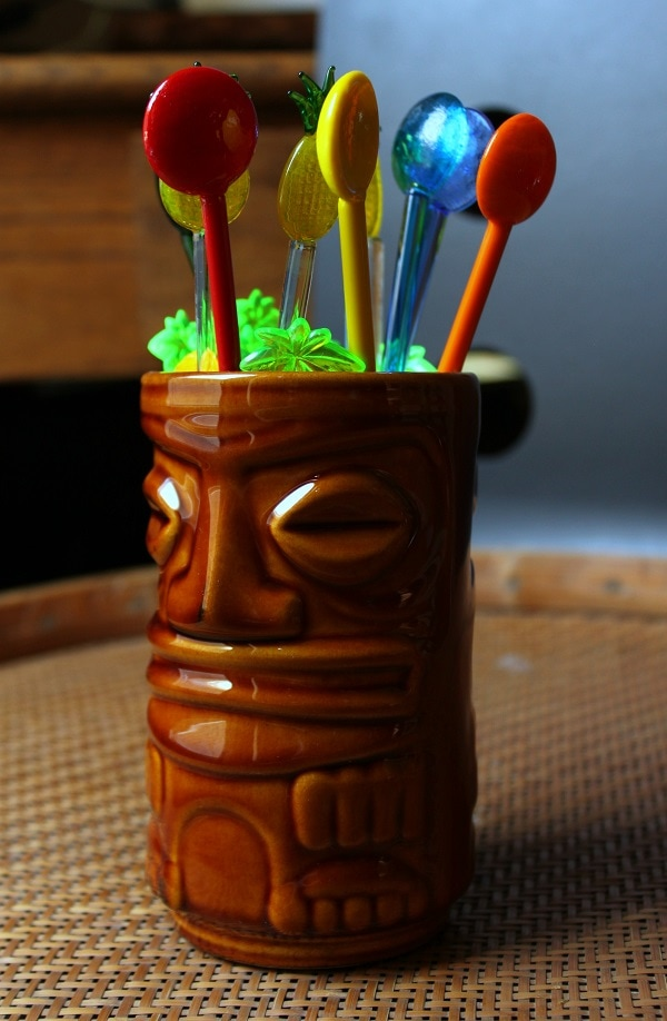 A brown glazed tiki mug containing stir sticks.