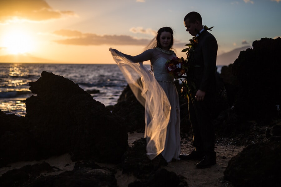 A wedding photo on a beach at sunset