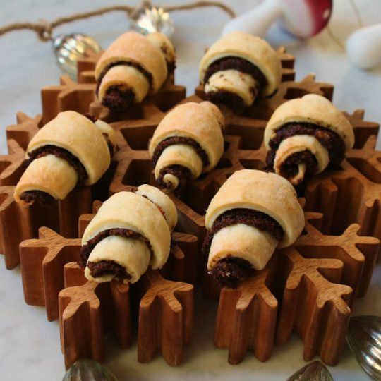 Rugelach rolled cookies sit on a wooden snowflake platter.