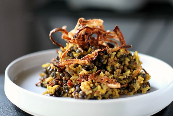 Mejadra - A white bowl filled with rice and lentils topped with golden fried onions.