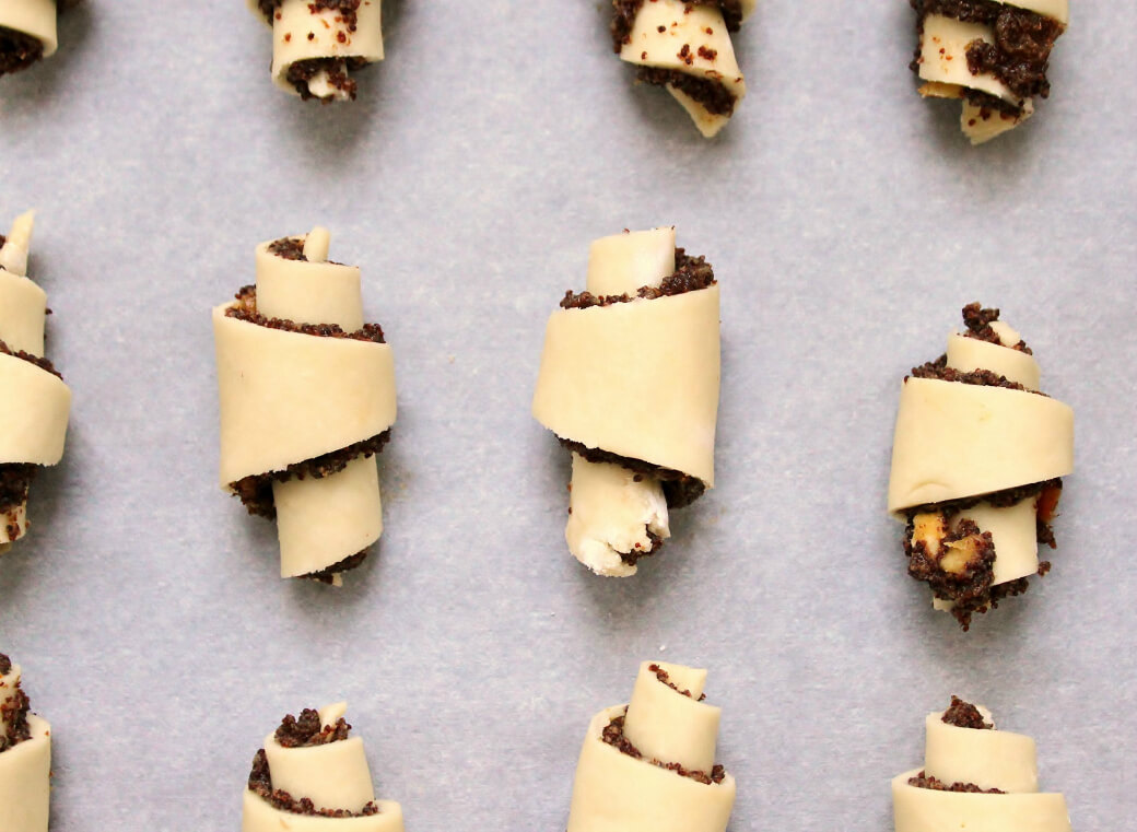 Rugelach - Rolled rugelach on parchment paper waiting to be baked.