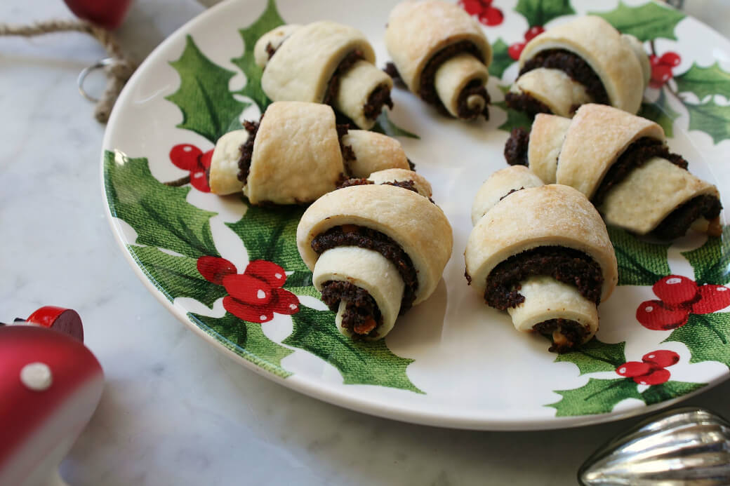 Rugelach - Seven rugelach arranged on a Christmas plate surrounded by Christmas decorations.
