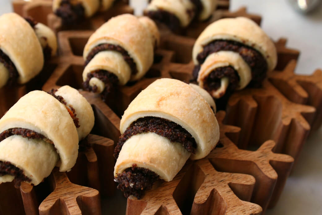 Rugelach rolled cookies on a wooden snowflake.