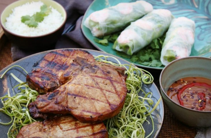 A platter of grilled pork chops and some Vietnamese Salad rolls.