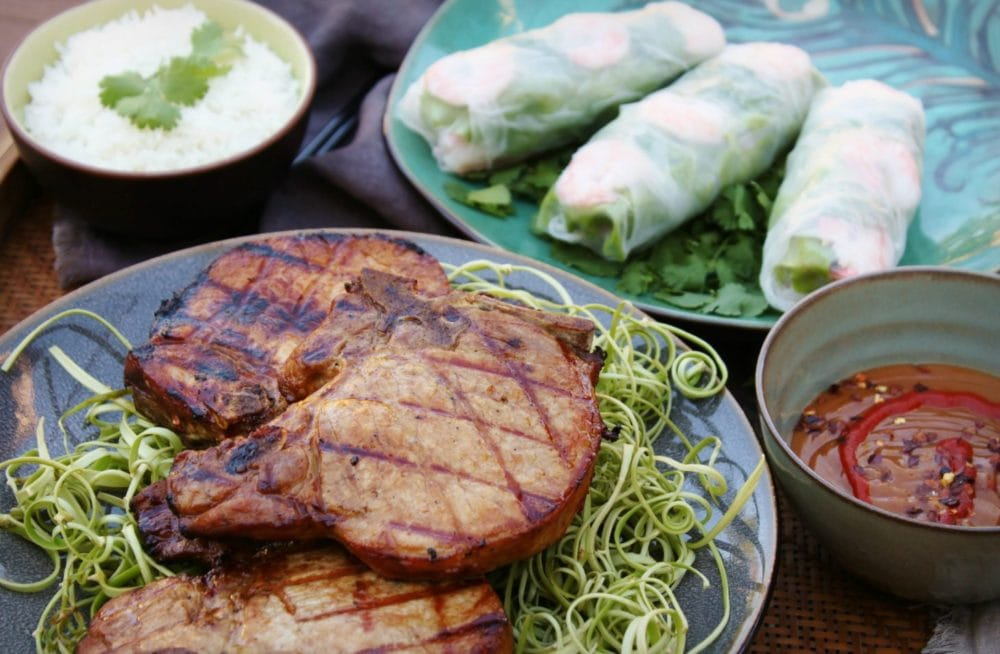 Three grilled Pork chops on a blue plate surrounded by a bowl of rice, spicy peanut sauce and salad rolls.