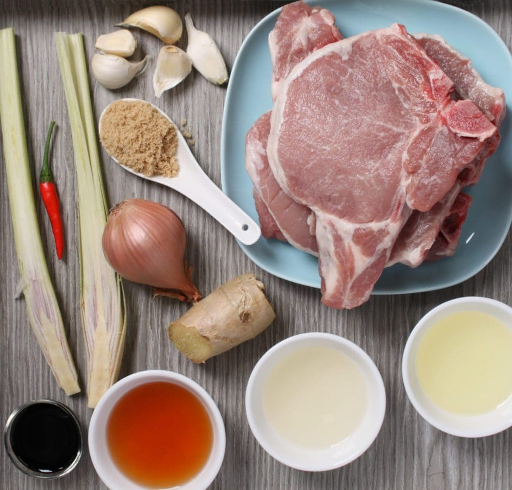 Raw Pork Chops and a selection of marinade ingredients on a grey background.