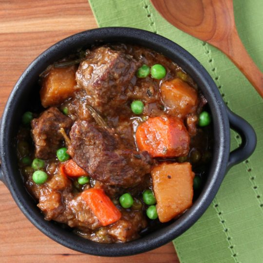A black bowl of Beef Stew containing large chunks of beef, carrots, rutabaga, and peas in a rich beefy broth.