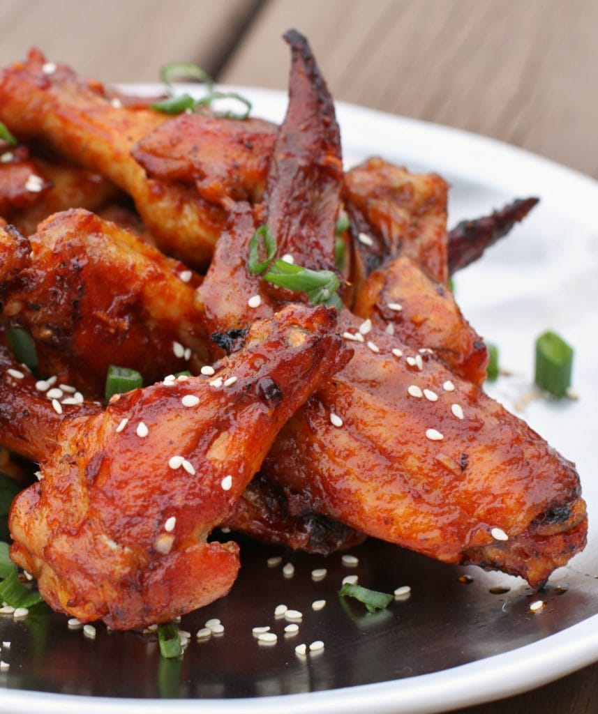 Pinterest image of a plate of wings coated with red sauce, sesame seeds, and green onions.