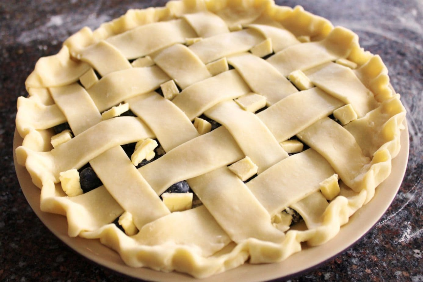 An unbaked pie with a lattice pastry top.