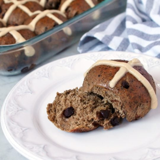Mocha and Chocolate Chip Sourdough Hot Cross Buns - A glass baking dish full of hot cross buns and a single bun on a white plate.